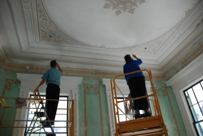 "Artists re-touch and in some cases re-create the wall and ceiling ""frescoes"" in the main house"