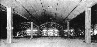 Construction view inside factory building. Traveling forms were used to construct roof barrels. Design gives bays 40x50 ft. between columns.