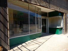 classic Post-WWII storefront, complete with diagonally placed window and separate showcase to the right of the door.