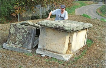 Figure 3. James Starnes behind box-grave monuments in the old Raymond cemetery made of Catahoula sandstone quarries at Mississippi Springs. Picture (color negative 601-24A) taken on December 19, 2006.
