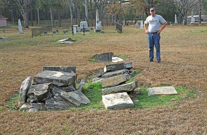 Figure 4. James Starnes standing behind the ruins of a box-grave monument in the old Raymond cemetery made from Catahoula sandstone quarried at Mississippi Springs. Picture (color negative 603-21) taken on December 19, 2006.