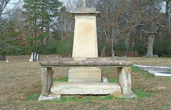 Figure 5. Alston family monuments in the old Raymond cemetery with death dates of 1838 (bench in foreground) and 1837 (tall monument in background). Monument stones are slabs of Catahoula sandstone from a quarry at Mississippi Springs. Picture (color negative 603-23) taken on December 19, 2006.