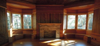 The east bedroom at the Charnley-Norwood House with its two window seats and curly pine walls. Photo by Susan Ruddiman