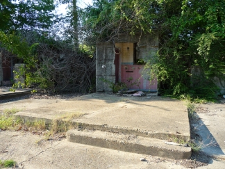Remains of a motel room, with concrete floor and bathroom in background