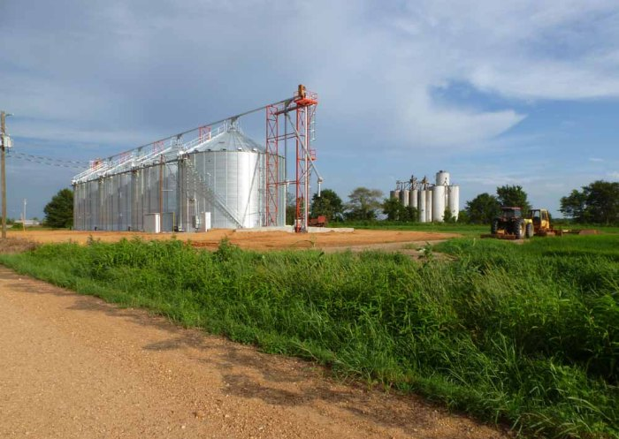 New metal silos with abandoned concrete silos across railroad tracks in the background.