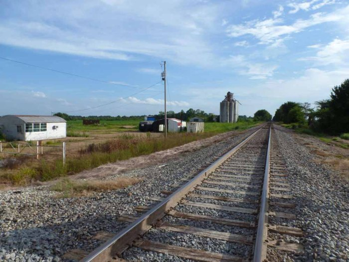 Concrete silo next to railroad tracks with an office building to far left.